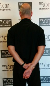 Todd Wegerski, chiropractor at the Joint-Morrisville demonstrates a shoulder stretch for neck pain.
